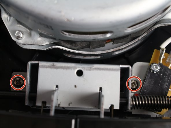 Remove the two 13.0mm screws that are holding down the button assembly using the Phillips #2 screwdriver.