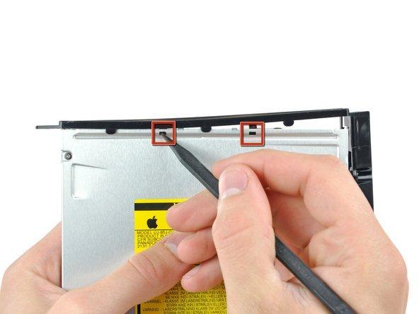 Avec la pointe d'un spudger, appuyez sur les pattes du support du lecteur optique pour les dégager des logements prévus à cet effet sur le dessus du lecteur optique.