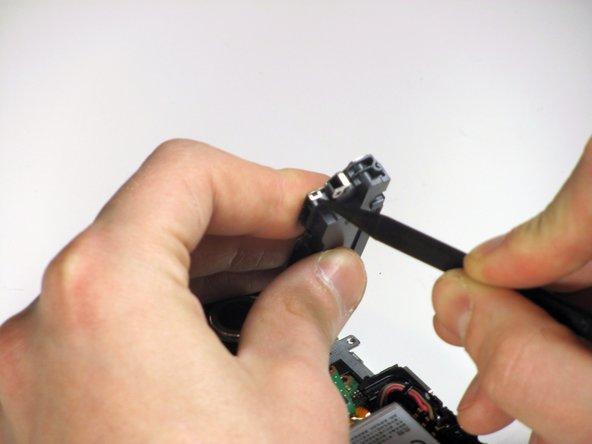 Using a spudger, remove the clips of the metal casing from each end of the USB drive.