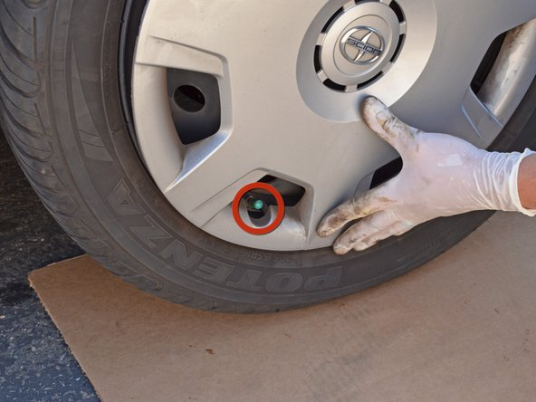 Place the wheel cover over the wheel and line up the semi-circular cutout of the wheel cover with the valve stem.