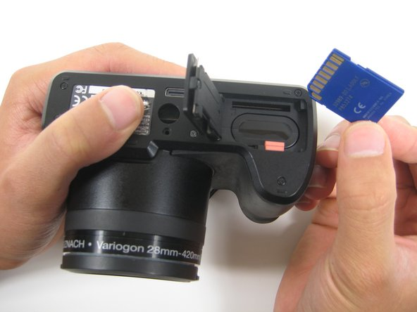 After removing the SD card from its locked position, gently pull the SD card out from the container to successfully remove it from the camera.