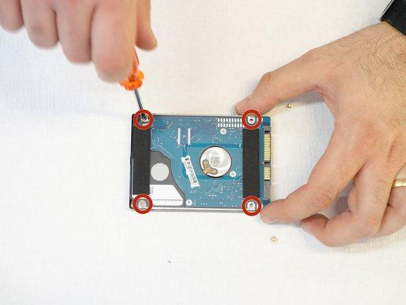 A l'aide du tournevis Phillips #1, enlever les 4 vis qui fixent le cache en plastique comprenant la languette avec laquelle on a débranché le disque.