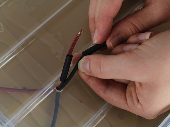 "Image 3/3: String heat shrink tubing onto both the red and the black solar panel wires separately using heat shrink that is between 3/16"" and 3/32""."