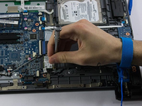 Once the screws are removed, the wireless card will tilt upwards. Firmly grab the card with one hand and pull it slowly, diagonally, out of the socket.