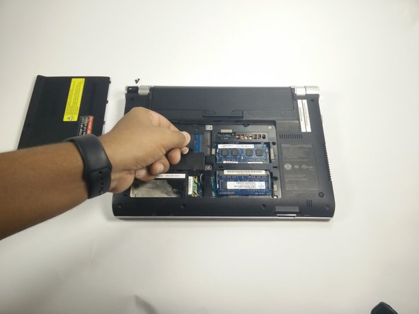 Image 1/3: Swiftly pull up on the tab to remove the hard drive.