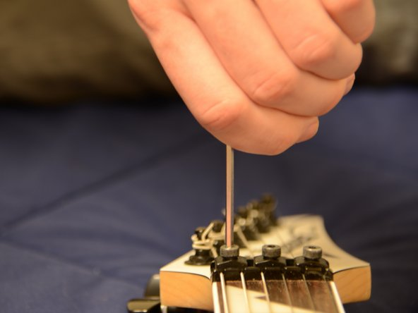 Unlock and remove the string clamps at the head of the guitar by using your allen wrench to unscrew the clamp.