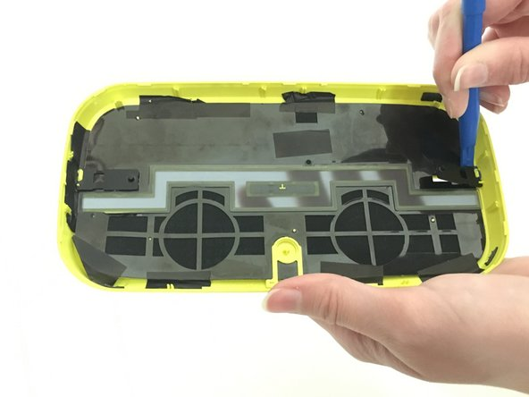 Using the plastic spudger, pry the button from the front plate of the speaker. The volume button is connected to the speaker by a plastic tab that has blue glue holding it down. The entire volume button can be removed from the front plate by carefully using the spudger to lift it up until it comes off.