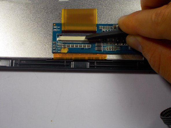 Image 2/3: Once the ribbon cable is loose, the tweezers should be used to slide the cable out.
