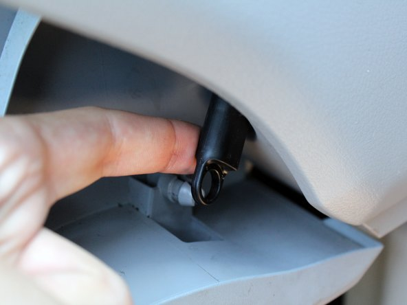 Move to the right side of the glovebox and gently pop off the black retaining arm.