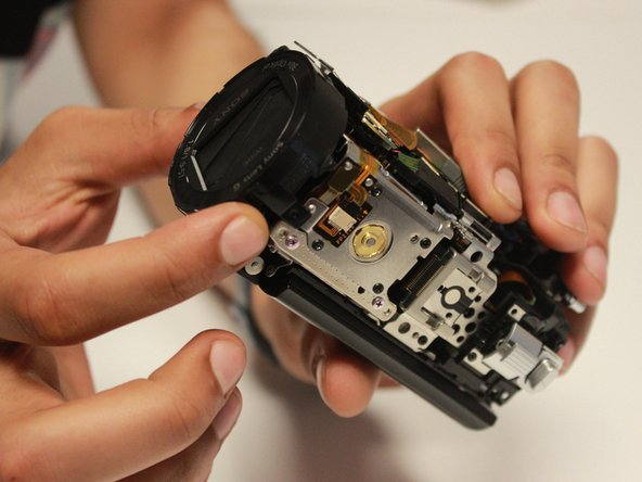 Hold the camera with your left hand, and gently remove the  shutter assembly part.