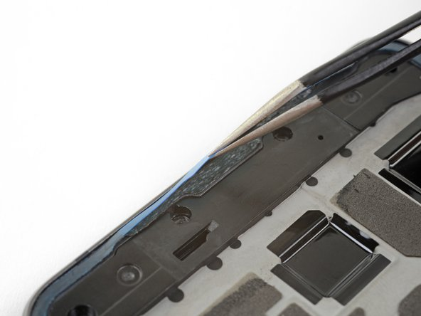Use tweezers to peel away the blue backing over top of the adhesive without peeling the adhesive off of the case.