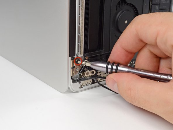 Image 1/1: While holding the display and upper case together with your left hand, remove the remaining T8 Torx screw from the lower (closer to the table) display bracket.