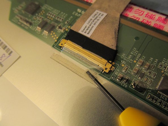 Image 1/2: Gently pry the small piece of tape away from the back of the LCD. This tape helps keep the LCD cable intact.