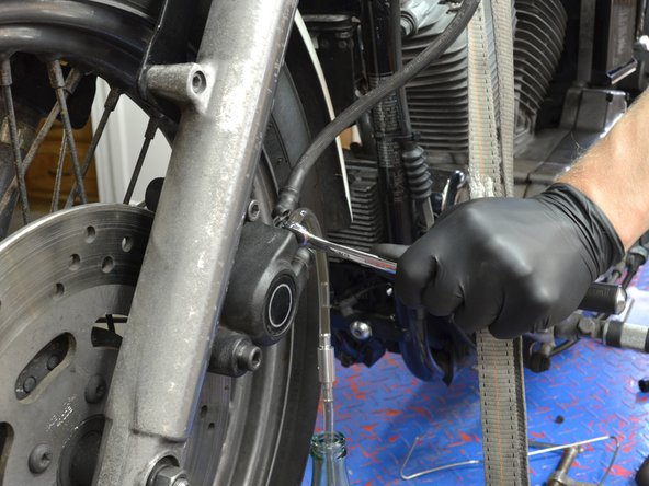 Continue to force more brake fluid out of the brake lines by depressing the front brake lever with your right hand.
