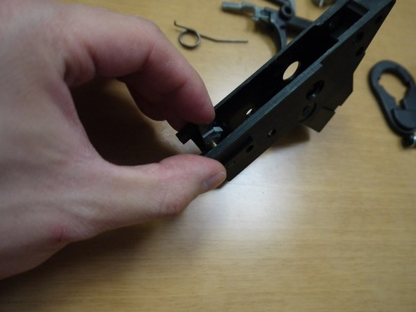 Insert the pin and brass spacer halfway in, then place the auto sear in as shown in the second picture. Push the pin all the way in. The spring leg that sticks out should point towards the FRONT of the gun.