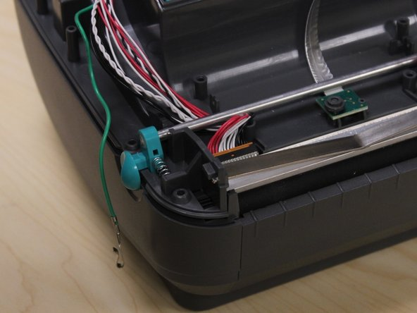 Thread the grounding cable away from the printhead and the lid latches.
