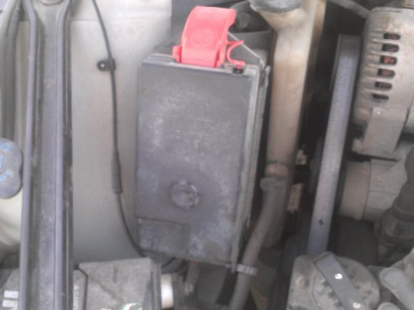 Image 1/3: Lift your hood and locate the housing for your fuses and relays. Next, remove the cover from the housing.