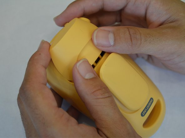 Image 1/1: Do this by holding the back side of the device upside down in your hands and applying pressure to the indented portion with both thumbs.