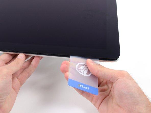 Procédez comme vous l'avez fait de l'autre côté : déplacez la carte lentement pour découper la mousse adhésive en veillant à ne pas exercer de pression excessive sur la vitre de l'écran.