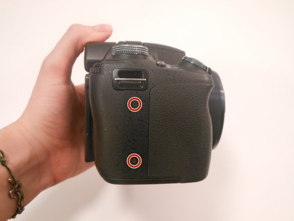 Image 1/3: Remove 2 screws on the side of the camera.