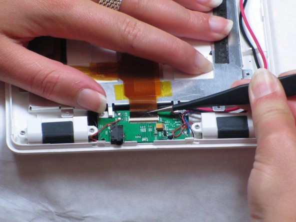 On the opposite end of the device: Remove the ribbon cable in between the speakers at the end of the battery.