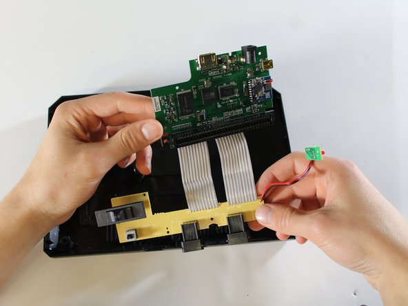 Gently remove the motherboard and the connected tan power switch board from the bottom plate.
