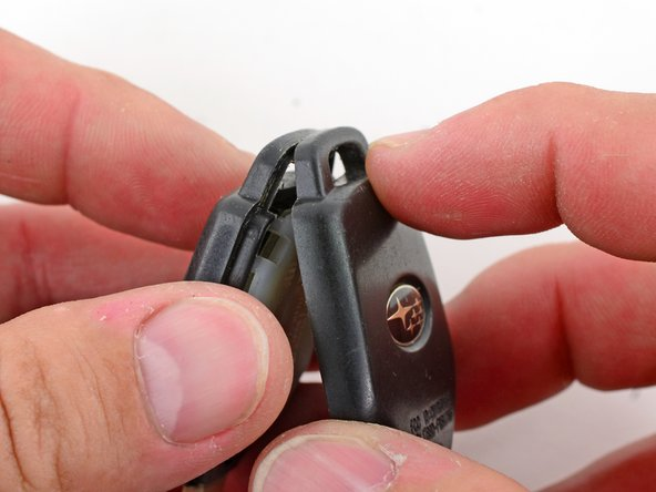 Image 2/2: Reattach the two halves of the key fob on the side opposite of the key first, then continue until the entire fob is back together in its original state.