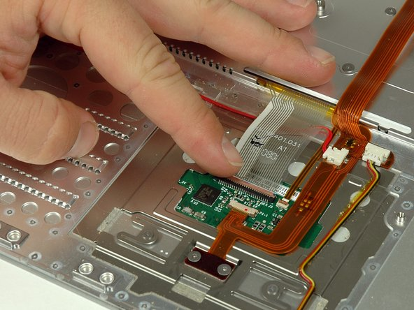 Use your fingernail to flip up the light brown plastic flap locking the keyboard ribbon cable in its socket.