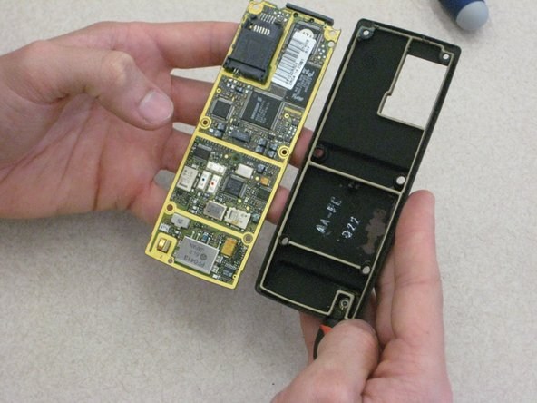 With one hand on the circuit board and one hand on the phone casing, carefully pull apart the circuit board from the front panel casing.