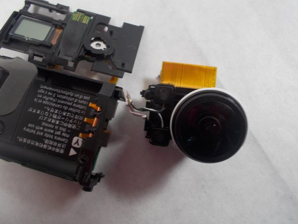 This will reveal the thick cable, carefully pull this cable towards the front. Next remove one last screw on the top of the device, and slowly pull the lens out. You'll notice that the microphone is still connected to the lens, just pop these out and the lens is off.