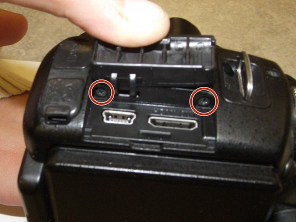 While you are on the left side of the camera, lift the HDMI / USB cover and remove the two screws that are hidden.