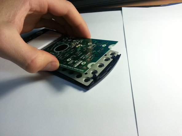 Carefully lift the circuit board while leaving the grey rubber piece face down.