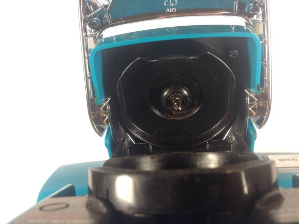 Image 2/2: Firmly place a finger on each one of the three tabs that hold the K-cup holder into place, pushing in lightly. The tabs are difficult to see, but they are there and will make the removal easier.  The top tab is located in the same location as the white triangle and the bottom two are located under the plastic bumps highlighted in the picture.