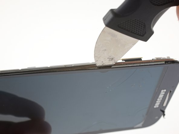 With the adhesive lose, insert the blade into the small gap between the frame and the screen, near the volume rocker.