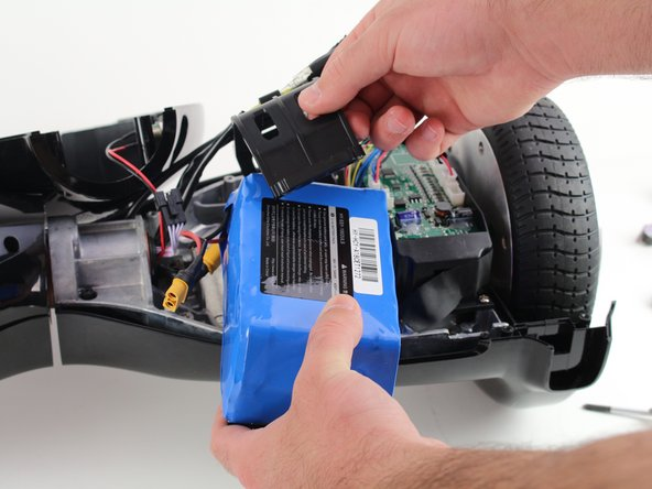 Gently lift the battery harness and remove the battery by lifting the battery and moving it away from the hoverboard.