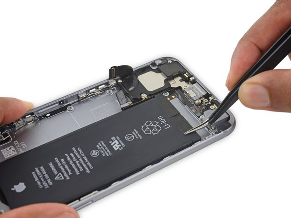 Use tweezers to peel up the tips of the battery adhesive strips at the lower edge of the battery.