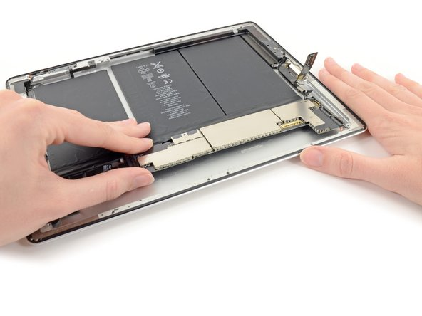 Lift the logic board out from the rear case and flip it over toward the battery.