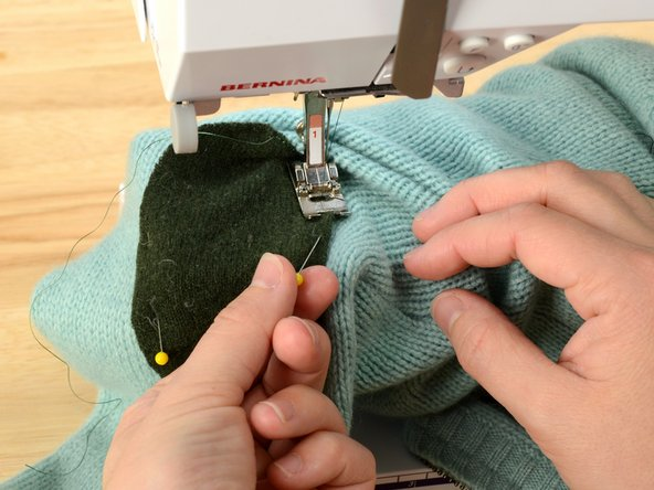 Sew around the edge of the patch, turning the sleeve as you go.