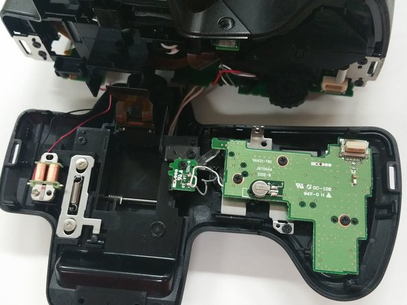 Image 2/2: Use the [product IF145-000 Plastic Opening Tool] to gently apply pressure on the top of the camera and remove the upper portion