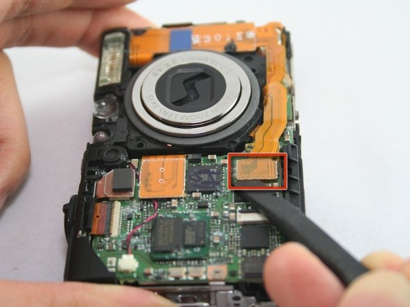 Use the spudger to remove the lens ribbon from the circuit board.