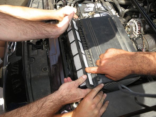 Once the air filter pops up, you can grab it with your hands and begin to remove it from the cover that is still being held open.