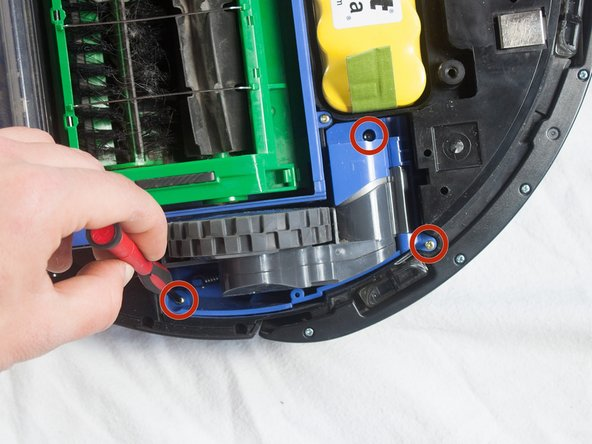 Find the blue wheel at the bottom of the Roomba, and unscrew the three captive screws holding it in place using a Phillips #1 screwdriver.