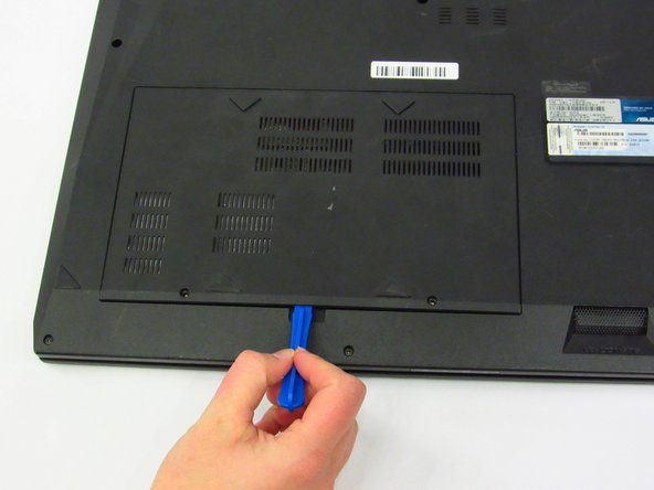 Insert the plastic opening tool into the small groove at the edge of the panel. Using the plastic opening tool, gently pry the back panel upward until it lifts free from the device. Gently lift the panel away with your fingers.