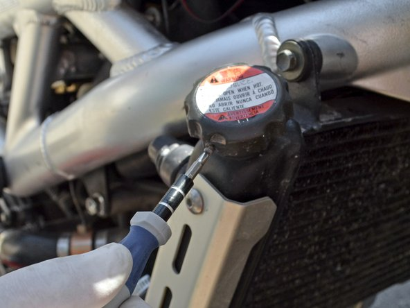 Remove the radiator cap security screw with a Phillips #1 screw driver by turning it counter-clockwise.
