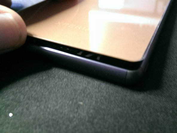 Image 2/2: Gently press it down along all edges and about two thirds down, where the cover sticks to the battery.