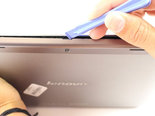 Image 1/1: Locate the small indentation in the plastic cover that runs across the top of the device.