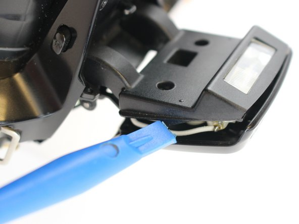Use a plastic opening tool to separate the  case that covers the flashbulb.