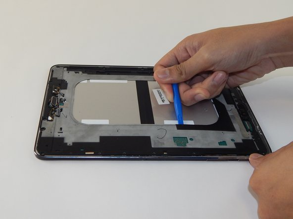 Pry open the next layer of the device using the plastic opening tool.