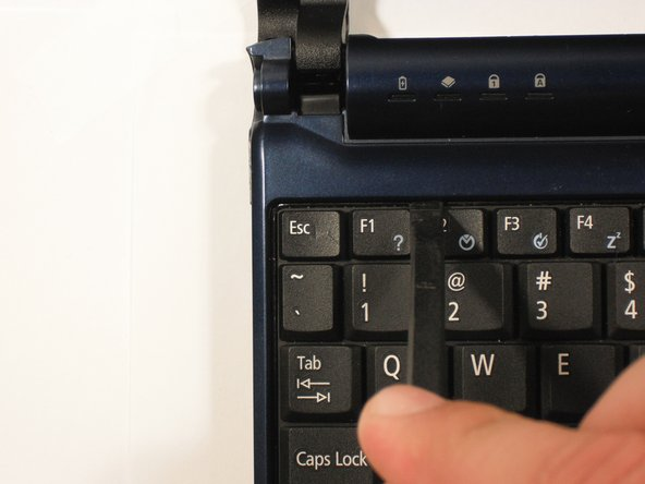 Image 2/3: Start with the spudger pointing towards the display and pry up to push each tab off the keyboard.