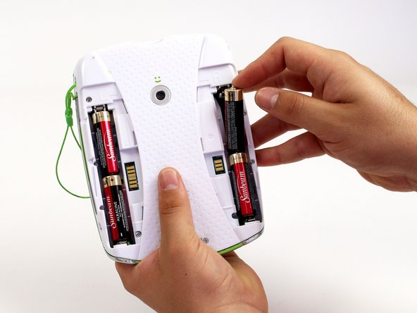 Push down from the positive end of the battery towards the negative end to pry the battery up out of its dispenser.